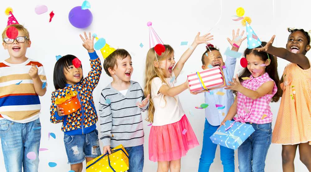 photograph of kids standing at a birthday party